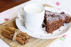 Chocolate cake in a white plate with cinnamon sticks Royalty Free Stock Photo