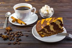 A chocolate cake on a white plate with a fork and a cup of black tea. A tea spoon. anise, coffee beans and a bowl of sugar cubes o. N dark wooden background Stock Images