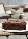 Chocolate cake on white plate, on hessian Stock Image