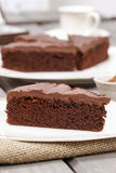 Chocolate cake on white plate, on hessian. Royalty Free Stock Photography