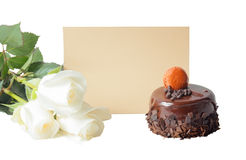 Chocolate cake, white roses and empty card for your text isolated Stock Images