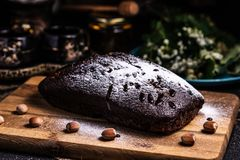 Chocolate cake on a wooden board with hazelnuts. Powdered icing. Chocolate Brownie royalty free stock image