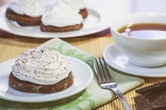 Chocolate cakes with egg white cream, a cup of hot tea, pieces of chocolate and a fork on a wooden table stock photos