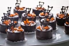 Chocolate cakes and orange. Chocolate cakes with orange chocolate shavings and chocolate decorations royalty free stock photos