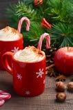 Chocolate caliente con crema azotada en tazas rojas Composición de la Navidad Foto de archivo