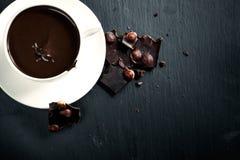 Chocolate caliente con el chocolate amargo en una pizarra negra Imagen de archivo libre de regalías
