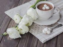 Chocolate caliente con el ramo de las melcochas y de los ranúnculos en oscuridad Imagen de archivo libre de regalías