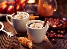 Chocolate caliente con la crema azotada, asperjada con canela aromático en las tazas blancas Imagen de archivo