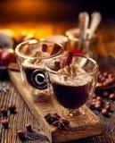 Chocolate caliente con la crema azotada, asperjada con canela aromático en las tazas de cristal Fotos de archivo libres de regalías