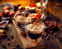 Chocolate caliente con la crema azotada, asperjada con canela aromático en las tazas de cristal Foto de archivo