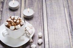 Chocolate caliente con la melcocha en la taza blanca y dos velas en la tabla de madera Fotografía de archivo libre de regalías