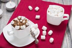 Chocolate caliente con la melcocha en la taza blanca y dos velas en la toalla roja en la tabla de madera Fotografía de archivo libre de regalías
