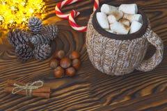 Chocolate caliente con las melcochas, el caramelo, las especias y las nueces en la tabla de la oscuridad del grunge Tarjeta de Ch Fotografía de archivo libre de regalías