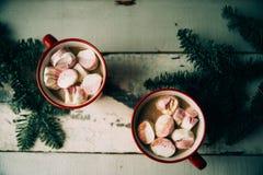Chocolate caliente con las melcochas en tazas rojas, cuadrado de la Navidad Imágenes de archivo libres de regalías