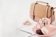 Chocolate caliente con las melcochas, la libreta y el bolso de las mujeres encendido Imágenes de archivo libres de regalías