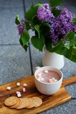 Chocolate caliente con las melcochas y las galletas de mantequilla selladas hechas en casa al lado de la lila Fotografía de archivo libre de regalías