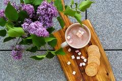Chocolate caliente con las melcochas y las galletas de mantequilla selladas hechas en casa al lado de la lila Fotos de archivo libres de regalías