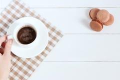 Chocolate caliente con los macarons en un fondo blanco Mujeres que sostienen la taza, efecto de la película Foto de archivo libre de regalías