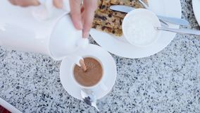Chocolate caliente de colada de la tetera a ahuecar para el desayuno metrajes
