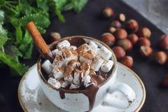 Chocolate caliente de la Navidad o del Año Nuevo con las melcochas, las nueces, la menta y el canela Foto de archivo libre de regalías