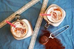 Chocolate caliente denso picante con el canela y la crema azotada adornados con el polvo de cacao en servilleta azul Imagen de archivo