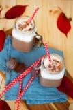 Chocolate caliente denso picante con el canela y la crema azotada adornados con el polvo de cacao en servilleta azul Imagenes de archivo