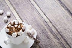 Chocolate caliente en la taza blanca con la melcocha en la tabla de madera Imagenes de archivo