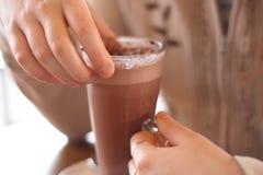 Chocolate caliente en manos de la muchacha Fotos de archivo