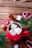 Chocolate caliente en taza roja con las melcochas imagen de archivo