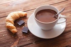 Chocolate caliente en una taza blanca con un cruasán en una tabla de madera Foto de archivo libre de regalías