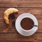 Chocolate caliente en una taza blanca con un cruasán en una tabla de madera Fotografía de archivo libre de regalías