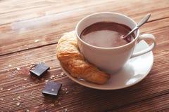Chocolate caliente en una taza blanca con un cruasán en una tabla de madera Imagenes de archivo