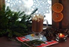 Chocolate caliente, melcocha, conos y ramas de árbol de navidad cerca de una ventana nevosa de madera Tarjeta de la Navidad y del Foto de archivo libre de regalías