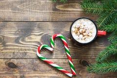 Chocolate caliente o cacao de la Navidad con las melcochas y el bastón de caramelo en el fondo de madera Espacio de la visión sup Fotografía de archivo libre de regalías