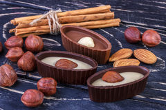 Chocolate candies, almonds, hazelnuts on wood background Royalty Free Stock Photo