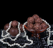 Chocolate candies assortment on plate. With white and black beads around Stock Image