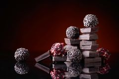 Chocolate candies with broken chocolate pieces on black reflecti royalty free stock image