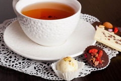 Chocolate candies, chocolate and cup of tea. Chocolate candies and cup of tea, horizontal, close up Stock Photography