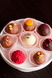 Chocolate candies, close up, vertical. Chocolate candies on white plate Stock Photo