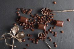 Chocolate candies and coffee beans. On shale board Stock Photography