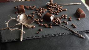 Chocolate candies and coffee beans. On shale board Royalty Free Stock Image