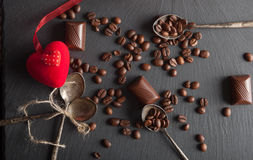 Chocolate candies and coffee beans. On shale board Stock Images