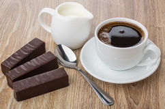 Chocolate candies, coffee in cup, spoon and jug of milk Royalty Free Stock Images