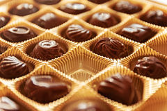 Chocolate candies of different shapes in a gold box, a perspecti Royalty Free Stock Images