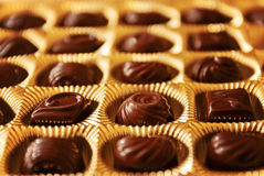 Chocolate candies of different shapes in a gold box, a perspecti Royalty Free Stock Photography