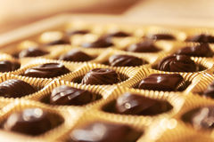 Chocolate candies of different shapes in a gold box, a perspecti Royalty Free Stock Photos