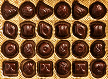 Chocolate candies of different shapes in a gold box, top view, s Stock Photography