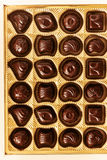 Chocolate candies of different shapes in a gold box, top view, s Royalty Free Stock Photos