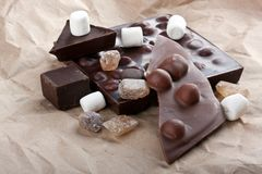 Chocolate, candies and marshmallows on a craft paper stock photos