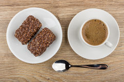 Chocolate candies with nuts in saucer, black coffee and spoon Stock Image